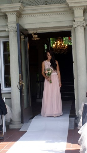 bridesmaid in pink dress walking down aisle at Hycroft Manor wedding ceremony