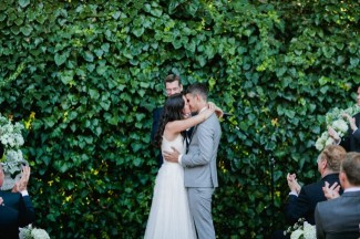 bride and groom kissing during backyard ceremony with ivy bush behind