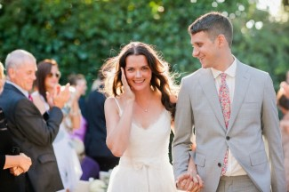 Bride and groom wearing grey suit and floral tie walking down the aisle after ceremony