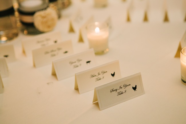 black and white escort card at Arctic Club Hotel wedding reception with picture of chicken and cow