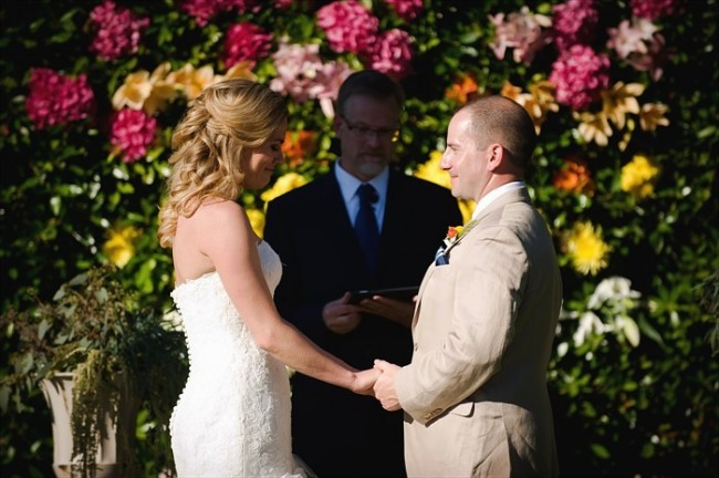 Bride and groom hold hands during backyard wedding ceremony with purple orange and yellow floral background