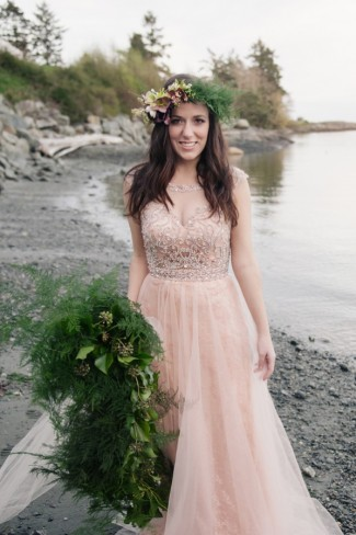 Bride on west coast beach wearing pink gown and floral crown.