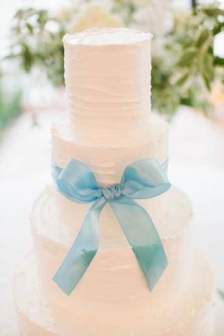 3-tier white wedding cake with blue bow