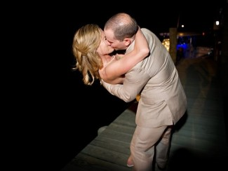 Bride and groom kissing on dock at night