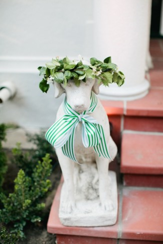 White dog statue on red stairs with green and white stripped bow around its neck and a leaf crown