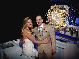 Bride and groom standing in boat with a just married sign at night