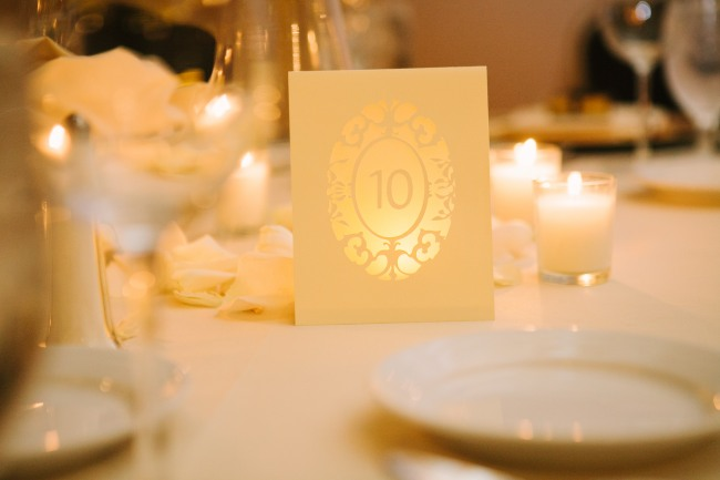 white paper with gold ornate border and table number
