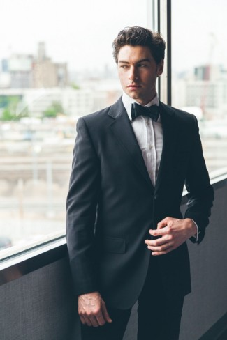 Groom in black tuxedo with black bow tie
