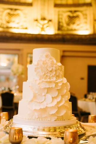4-tier white wedding cake with big white flower petals on silver tray