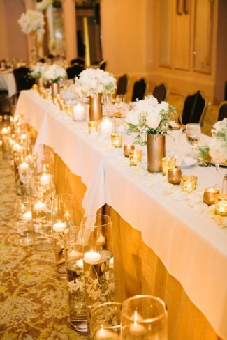 bridal party table with gold candles on table, gold vases with white flowers and floating candles in vases lining the front