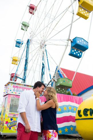 Engaged couple kissing in front of ferris wheel