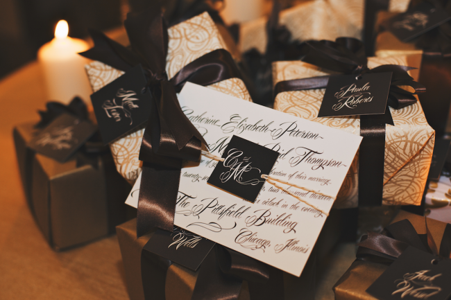 Wedding reception favors boxes wrapped in gold paper and brown ribbon