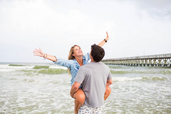 guy holding his fiancee up standing in the water with her hands in the air