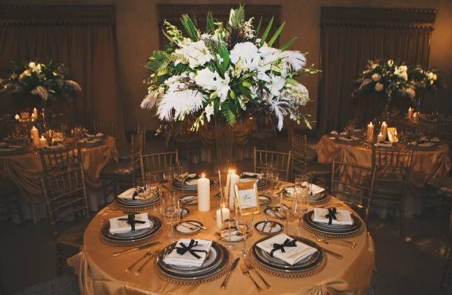 Tall clear vase with feather, hydrangeas, lilies in the center of gold tablescape