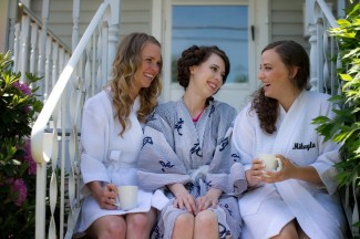 Bride with 2 bridesmaids in silk robes sitting on stairs of porch with coffee