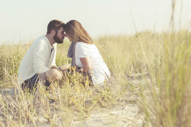 13 a couple head to head sitting in the grass on the beach