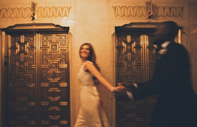 Bride and groom holding hands and running down the hall of elevators at the Pittsfield Building