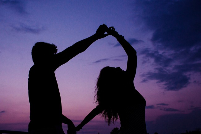 Couple standing on a river at dusk dancing with purple and blue night sky behind