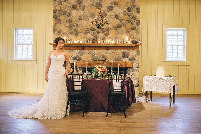 bride next to table in front of warm fall wedding shoot fireplace