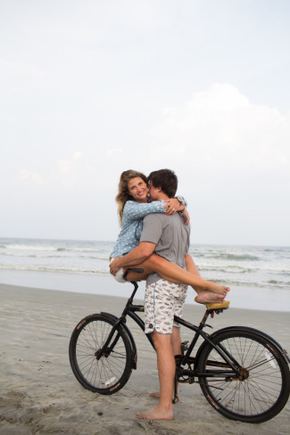 girl looking at camera sitting on handle bars of bike on the beach with her fiance