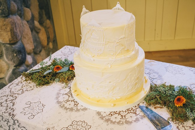 2 tier white with yellow accent wedding cake with bird cages made by Cake Studio