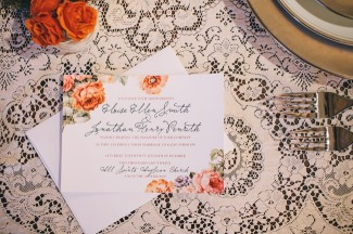 Vintage orange and pink roses on wedding invitation made by Join Design on lace table