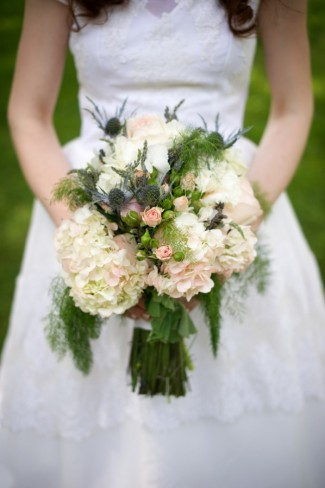 Bride carrying white hydrangeas and thistles and pink spray roses bridal bouquet