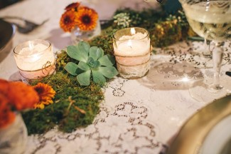 moss with succulents and orange flowers as center piece with white candle covered in lace