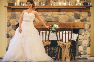 bride standing in strapless sweet heart neckline with her hand on a chair with a burlap bow