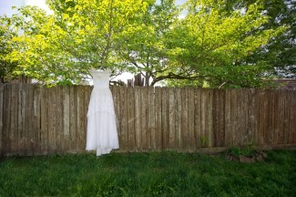 backyard fence with white wedding dress hanging from tree
