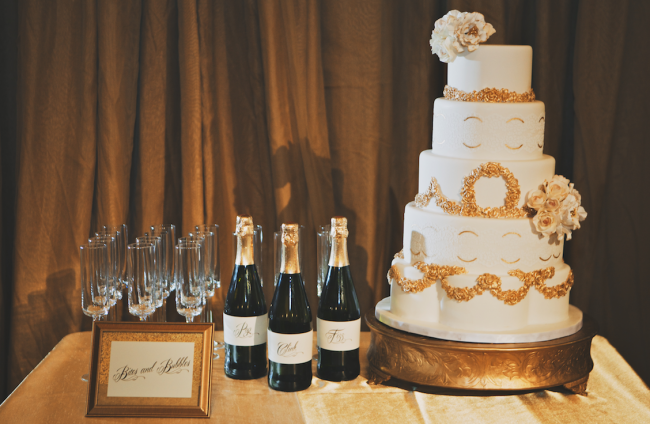5 tier white wedding cake with gold accents and 3 champagne bottles with flutes on table