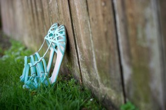 Blue sandal shoes for bride leaning up again a fence