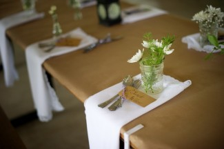 picnic table place setting with white napkins, mason jar of white flowers, black lanterns at Firestone Metro Park Wedding
