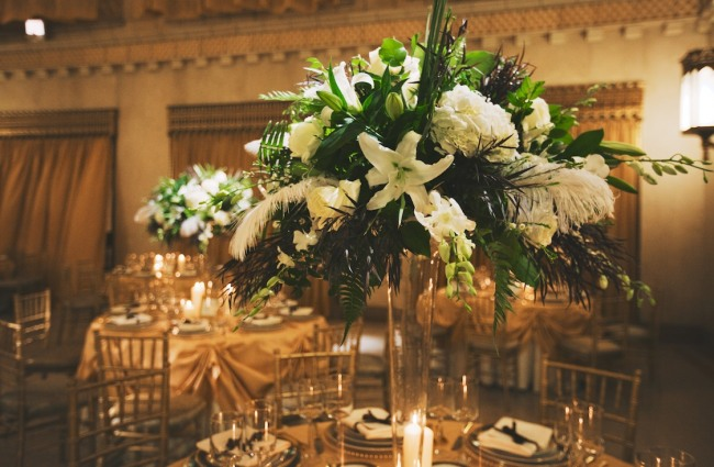 Tall clear vase with white feather, lilies, hydrangeas and green foliage as wedding reception centerpiece