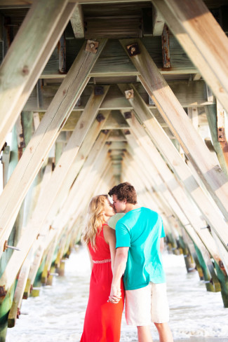 Couple kissing and holding hands under a dock on the beach