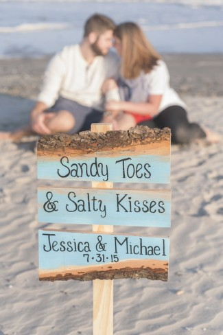 wood sign on beach announcing couple's wedding date