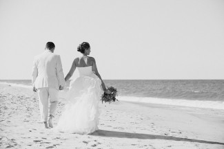 Black and white photo of bride and groom walking on the beach holding hands
