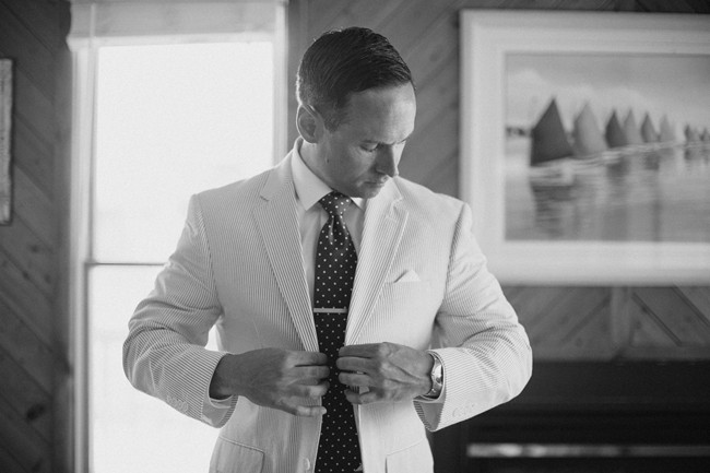 Black and white photo of groom getting ready wearing blue and white pin stripped suit