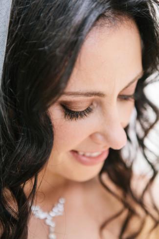 Brown hair bride with brown eye shadow wearing bridal veil looking downwards