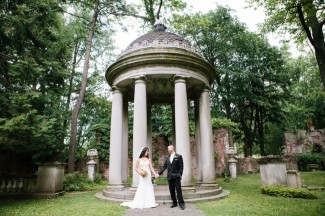 Bride and groom holding hands in front of dome arch at Elegant Westchester Alder Manor House Wedding