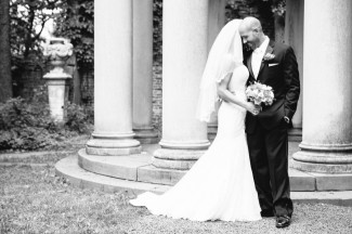 Black and white photo of Bride and groom hugging in front of dome arch at Alder Manor House Wedding