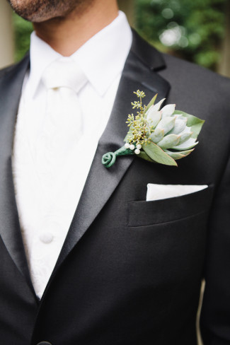 Groom wearing white tie with tux and a Succulents boutonniere on lapel