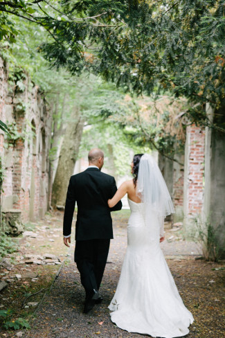 Bride and groom arm in arm walking down path at Westchester Alder Manor House