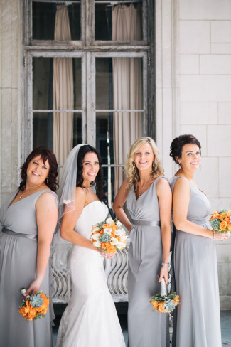 Bride wearing veil standing with 3 bridesmaids wearing grey david's bridal gowns