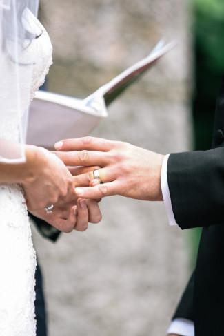 Bride putting wedding band on grooms finger during Westchester Alder Manor House wedding