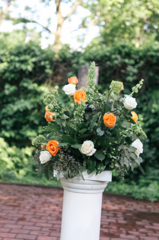 Wedding ceremony floral arrangement with orange and white roses on a pedestal