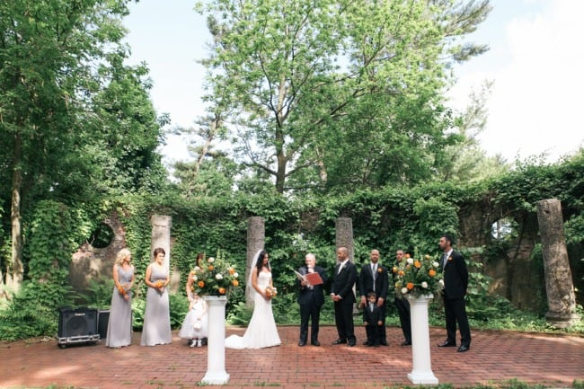 Outdoor wedding ceremony with pedestal and flowers at Alder Manor House
