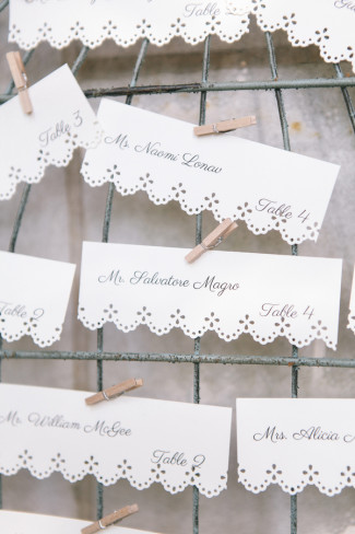 White escort cards with mini clothes pegs attached to birdcage