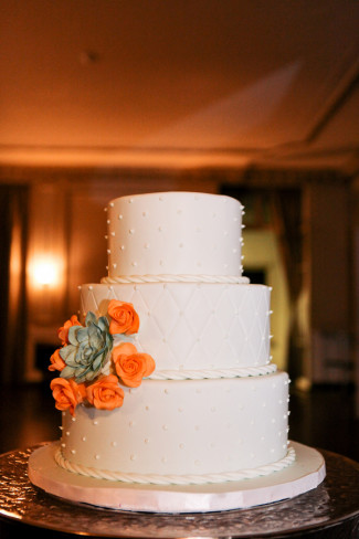 3 tier white cake with swiss dots and orange roses and succulent plant