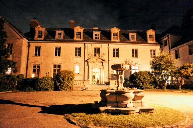 Photo of Alder Manor House at night with circular driveway and fountain
